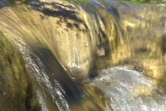 A stream flows over small rocks. Stock Footage