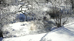 Hoarfrost and snow cover the banks of a brook in winter Stock Footage