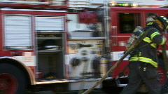 Fireman Pulls Hose by Firetruck Stock Footage