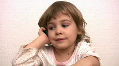 Little girl talks by phone Stock Footage