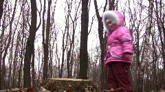 Little girl jump from stub in winter park Stock Footage