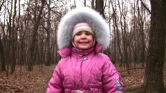 Walking little girl in winter park to camera Stock Footage