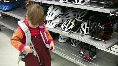 Little girl with knapsack in shop bicycle helmets Stock Footage