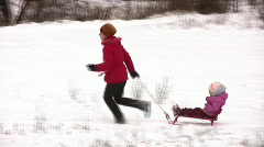 mother with little girl on sled - stock footage