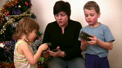 Woman with children consider toys near christmas tree Stock Footage