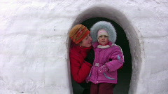 Mother with small girl looks from snow building Stock Footage