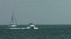 Power Boat in ocean heading toward camera with sailboat in background  Stock Footage