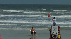 Beach Life guard watching over swimmers in the ocean surf  Stock Footage