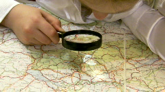 Girl with magnifier studies a map of Europe. Stock Footage