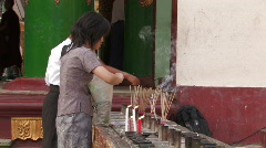 Myanmar: Lady burns incense at a Buddhist temple. Stock Footage
