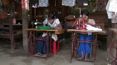 Myanmar: Women sew on foot pedal sewing machines Stock Footage