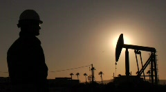 Oil worker wiping brow - stock footage
