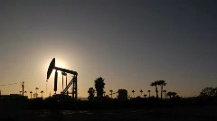 Oil Pump silhouette, worker walks through frame Stock Footage