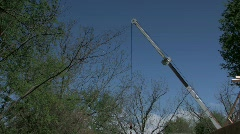 Aerial crane hoisting roof joist into place against blue sky with audio  Stock Footage