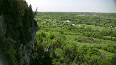 Rocky cliff overlooks the grassy fields and treetops (High Definition) - stock footage