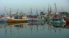 Pan across moored fishing cutters reflected in the water. Stock Footage