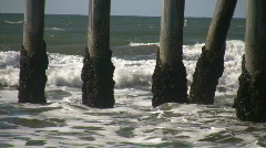 Ocean waves splash against the pier's support columns (High Definition) Stock Footage