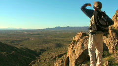 Hiker looking over edge of cliff - HD  Stock Footage