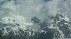Clouds Swirl Around Snowy Moutain Tops Stock Footage