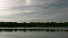 Serene scene of quiet lake, reflecting the treeline (High Definition) Stock Footage