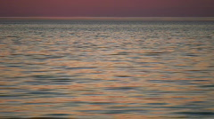 Water's surface reflects the orange sky at dawn (High Definition) Stock Footage