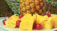 Pineapples and cherries rotating on dish  Stock Footage