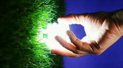 Energy saving light bulb turning on as it's screwed into green grass, vertical - stock footage