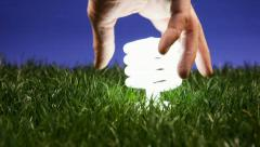 Energy saving light bulb turning on when screwed in green grass  - stock footage