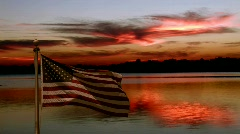 American flag flying at sunset over lake - stock footage