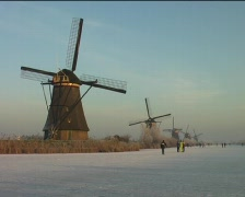 Traditional dutch: Ice skating along windmills Stock Footage
