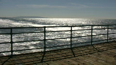 Ocean sparkles and moves from beyond the boardwalk (High Definition) Stock Footage