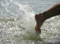 High speed camera : Girl steps into ocean waves Footage