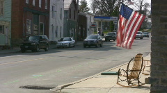 Small Town Main Street USA With Flag Flying From A Store Stock Footage