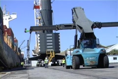 Derrick cranes in harbour loading ship Stock Footage