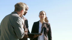 Three businesspeople having a meeting outdoors Stock Footage