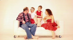Family four with two children sit on sofa Stock Footage