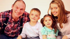 Family four with two children peer into camera and smile Stock Footage