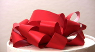 Red bow on revolving box Stock Footage