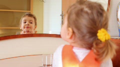 Small girl before mirror combs hairs Stock Footage