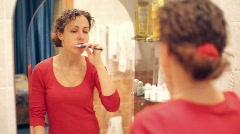 Woman before mirror cleans teeths Stock Footage