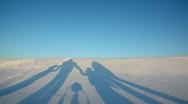 Family walk behind on snow hill on sundown Stock Footage