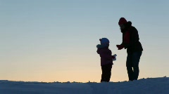 Silhouette mother with child throw snow Stock Footage