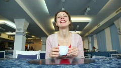 Woman drinks coffee in cafe Stock Footage