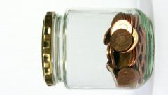 Savings. Coins being added to a penny jar. Stop motion animation. Stock Footage
