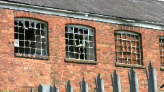 Broken windows of a closed and derelict factory building. England UK Stock Footage