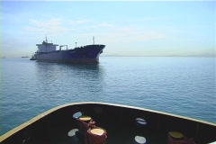 Tug approaching tanker medium wide shot Stock Footage