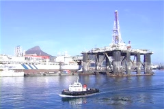Tug passes drill rig in harbor Stock Footage