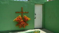 Cross and flowers on bright green wall. - stock footage