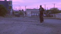 Bum walking through rail yard at dusk Stock Footage