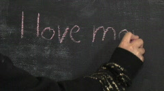 Child Writes I Love Mommy for Mother's Day on a Chalkboard Stock Footage